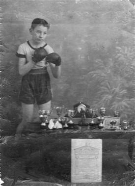 Photo:Ted Thomson (senior) displaying some of his boxing trophies in the 1930s
